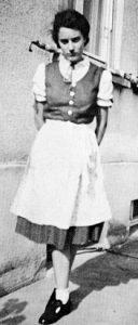 """Hannie Baer am 1. September 1939, am Tag des Beginns des Zweiten Weltkriegs. Das Foto ist aufgenommen in der Ulmer Steinhövelstraße 5, vor dem Haus von Rosa und Wilhelm Lebrecht. Hannie schreibt: """"Wir feierten an diesem Tag Wilhelms 59. Geburtstag. Mitten in der Feier hörten wir vom Kriegsausbruch. Da verging uns die Feier-Stimmung , was auch der ernste Ausdruck auf meinem Gesicht zeigt. Ich trug ein modernes Dirndl, samt neuer Frisur und neuen Schuhen."""" (""""Child of Two Worlds, S. 131)."""